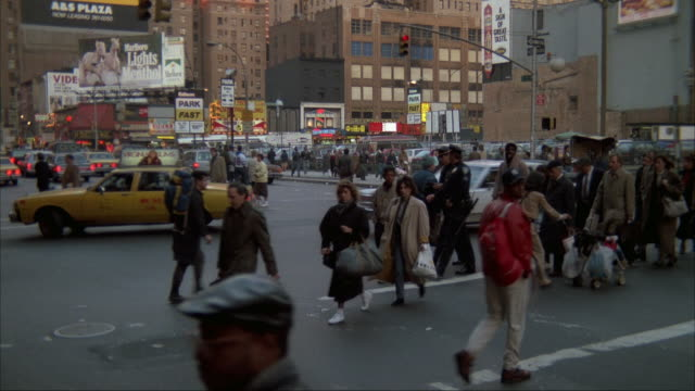 vídeos de stock, filmes e b-roll de medium angle of city street intersection in new york city from street corner. traffic heading top left, pedestrians cross crosswalk across shot. marlboro billboard and buildings in background. - 1980 1989