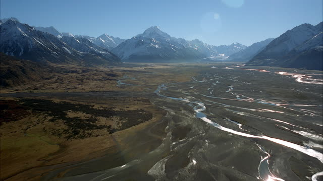 AERIAL OF DIRT FLATLANDS OF VALLEY BETWEEN SHARP SNOW COVERED MOUNTAIN PEAKS. SEE GLEAMING STREAMS SCAR THE FLATLANDS. JET POV FLIES OVER SMOOTH MUDDY LANDS. PICKS UP SPEED. FLIES TOWARD MOUNTAINS WHILE STAYING CLOSE TO GROUND.