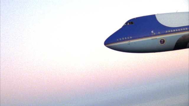 medium angle of air force one descending to left over layer of clouds on bottom. see united states of america and american flag on tail wing. - エアフォースワン点の映像素材/bロール