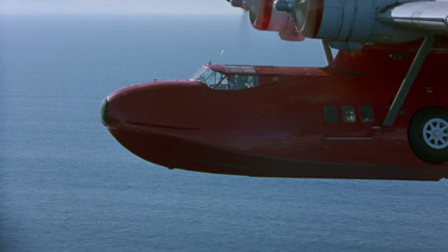 aerial to aerial of red seaplane or water plane flying above ocean. shot begins with close angle of cockpit and propellers, then pulls back and moves above to high angle down. - propeller video stock e b–roll