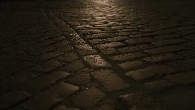 close angle on brick paved, cobblestone road. camera pans up to city street filled with cars and taxis as two females walking on street. see people walking on sidewalk alongside of city street. neg cut. - kopfsteinpflaster stock-videos und b-roll-filmmaterial