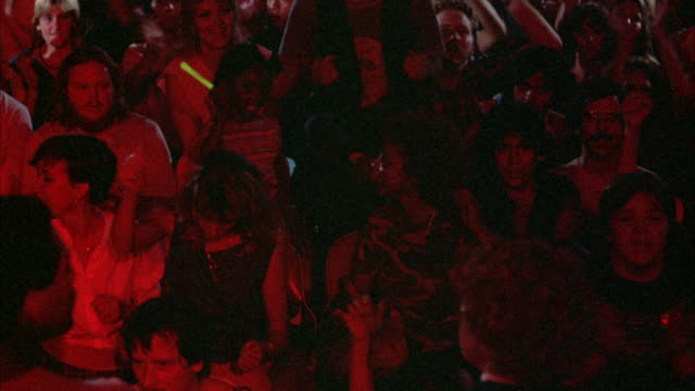 MEDIUM ANGLE. YOUNG ROCK CONCERT AUDIENCE SITTING IN CHAIRS DRESSED IN EARLY 1980'S ATTIRE, CHEERING AND DANCING TO MUSIC, WITH ARMS IN THE AIR, CLAPPING AND PUMPING THE AIR.