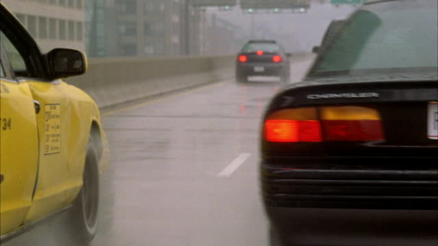 tracking shot of gray plymouth voyager suv. see suv move forward on highway with other traffic. heavy rain falling. see chrysler compact car weave into pov - compact car stock videos and b-roll footage