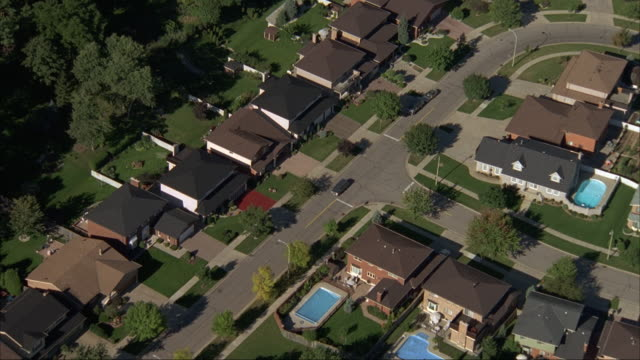 aerial tracking shot of car driving through winding residential community area with tract housing. see only rooftops. some swimming pools in backyard. - tract housing stock videos and b-roll footage