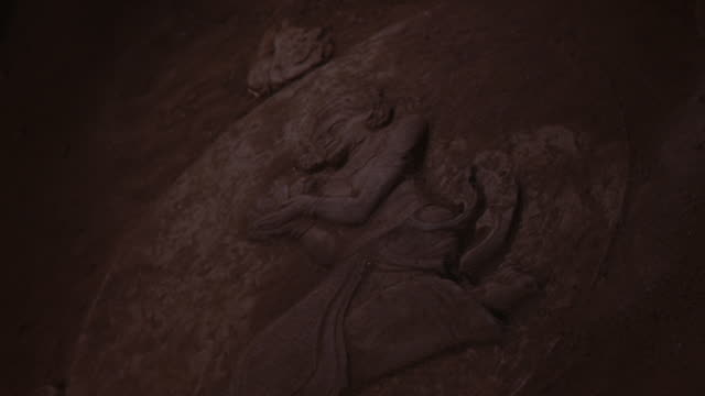 CLOSE ANGLE OF BAS RELIEF STONE CARVING OR SCULPTURE OF WOMAN WITH HANDS CUPPED. LIGHT SHINES ON CARVING WITH INCREASING BRIGHTNESS. COULD BE UP ANGLE OF DIRT WALL, OR DOWN ANGLE OF TEMPLE FLOOR. ASIAN ART.