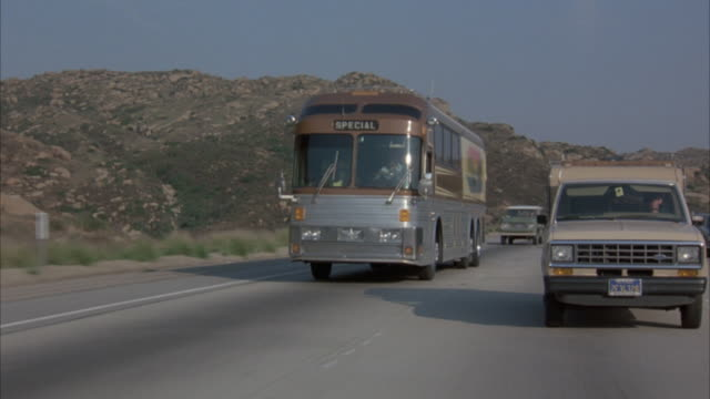 wide angle of oncoming traffic on desert highway with metal tour bus and pickup truck driving side by side. painted image of ship on water on side of tour bus. truck cuts in front of tour bus. bus drives closer to camera and out of shot. - tour bus stock videos and b-roll footage