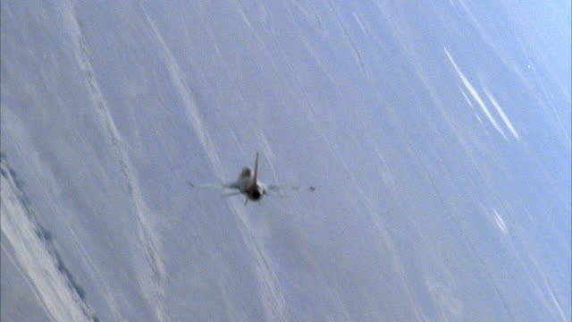 TRACKING SHOT OF A CAMOUFLAGE F-16 FIGHTER JET FLYING. THEN SEE TWO OTHER F-16 FIGHTER JETS BANKING AND ENGAGING IN A DOGFIGHT. SEE LAND BELOW. NEG CUT. ACTION.