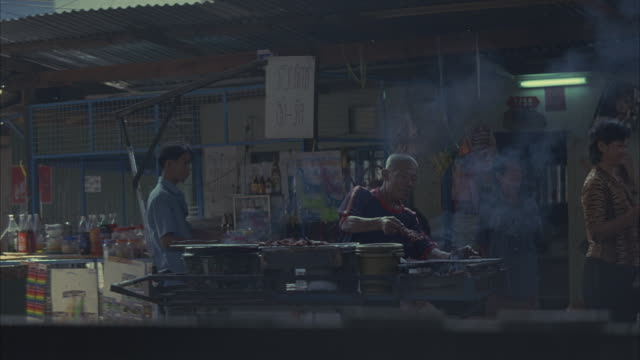 MEDIUM ANGLE OF OPEN AIR MARKET. SEE SEVERAL VENDORS SELLING GOODS IN FRONT OF MARKET BUILDING. SEE ASIAN VENDOR COOKING BBQ SKEWS ON PORTABLE BURNERS. SEE STEAM RISE FROM BBQ. SEE PEOPLE AND OTHER FOOD AND DRINKS IN BACKGROUND.