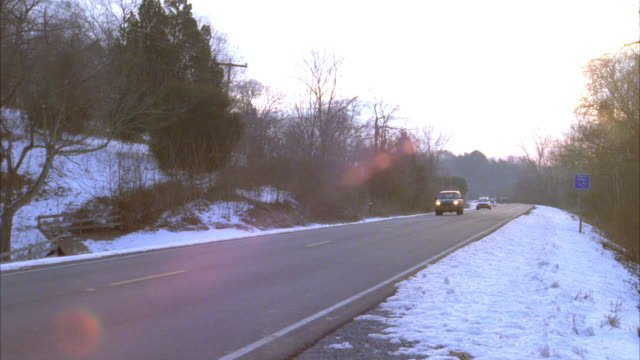 medium angle of country road with snow on sides. see sun setting low in sky. camera pans left to follow green ford explorer turn right off road into driveway of estate. house cannot be seen. - 1998 stock-videos und b-roll-filmmaterial