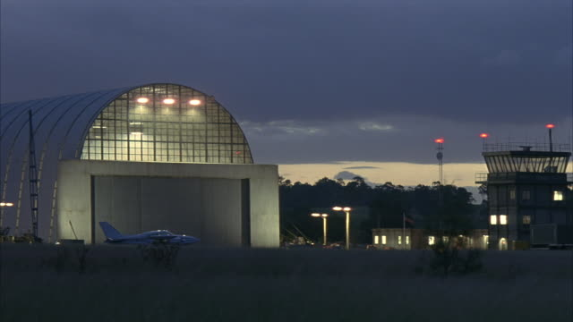 vídeos de stock e filmes b-roll de wide angle of hangar at night in lit small airport. small jet in front of hangar. control tower on right of screen. field of tall dry grass  in foreground. dark gray clouds and waning sunlight in sky. - hangar