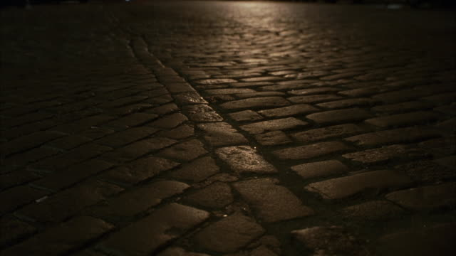 close angle on brick paved, cobblestone road. camera pans up to city street filled with cars and taxis as two females walking on street. see people walking on sidewalk alongside of city street. - cobblestone stock videos & royalty-free footage