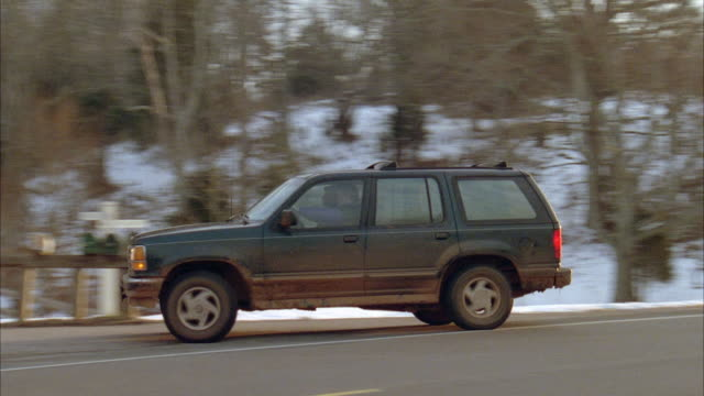 stockvideo's en b-roll-footage met tracking shot of green ford explorer driving along country highway. drives from right and enters long, secluded driveway. sun halations at beginning. - 1998