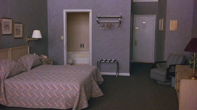 vídeos de stock, filmes e b-roll de medium angle of dimly lit gray hotel or motel room. see luggage rack below empty hangers on metal rack  at left. see restroom and full size bed at left. see partial dresser with lamp at right. - hóspede