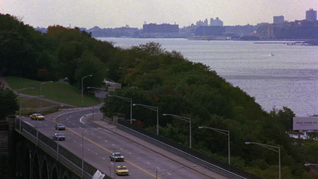 HIGH ANGLE DOWN OF CURVING FOUR LANE STREET ALONG HUDSON RIVER. COULD BE RIVERSIDE DRIVE IN BROOKLYN. SEE THICK NONCONIFEROUS TREES LINING HILL ALONGSIDE ROAD. SEE RIVER AT RIGHT. SEE CITY SKYLINE AT FAR SIDE OF WATER. COULD BE NEW JERSEY SHORE.