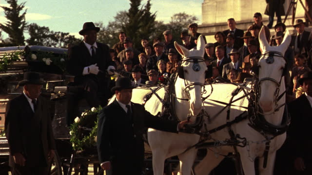 medium angle of state funeral in front of louisiana state capitol building at baton rouge. coffin or casket in glass-cage horse drawn carriage hearse. police officers walk in funeral procession.  government buildings, flowers. crowd of mourners. - carro funebre video stock e b–roll