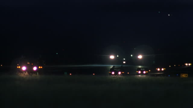 PAN RIGHT TO LEFT OF AIR FORCE ONE JET DRIVING DOWN RUNWAY IMMEDIATELY FOLLOWED BY SEVERAL EMERGENCY VEHICLES WITH LIGHTS AND SIRENS ON