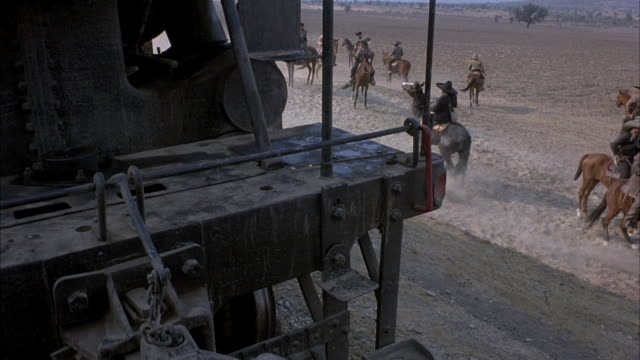 medium angle of locomotive of steam engine train in left foreground and about ten mexican cowboys on horseback on right, horseback riding. cowboys have hand guns drawn. train and pov start moving on tracks. - locomotive stock-videos und b-roll-filmmaterial