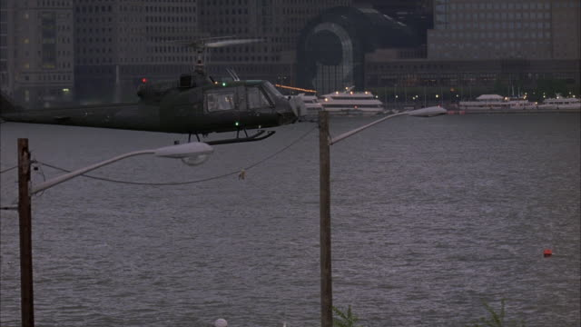wide angle of helicopter hovering in air.  see new york city skyline in background.  pan left to right of helicopter flying in sky, lands on landing pad on dock in middle of river .see soldiers walking around dock. - helicopter landing stock videos and b-roll footage