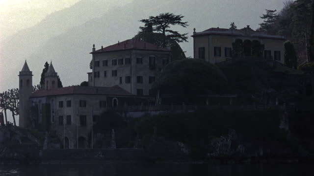 medium angle of multi-story, split-level, upper-class, renaissance, 15th to 17th century villa or castle on waterfront. see staircase leading down to boat dock in foreground. see red tiled roof and two towers of villa. - https点の映像素材/bロール