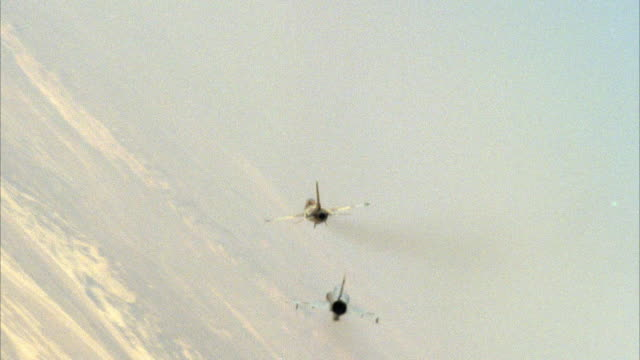 TRACKING SHOT OF TWO CAMOUFLAGE F-16 FIGHTER JETS FLYING. SEE JETS ENGAGING IN A DOGFIGHT, BANKING AND BARRELING. SEE LAND BELOW. NEG CUT. ACTION.