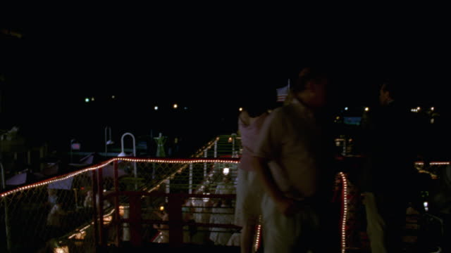 WIDE ANGLE MEN AND WOMEN TALKING OR SOCIALIZING ON DINNER CRUISE OR PARTY ON BOAT. COULD BE YACHT CLUB OR COUNTRY CLUB EVENT IN MARINA. RIVERBOAT WITH LIGHTS AND AMERICAN FLAG.