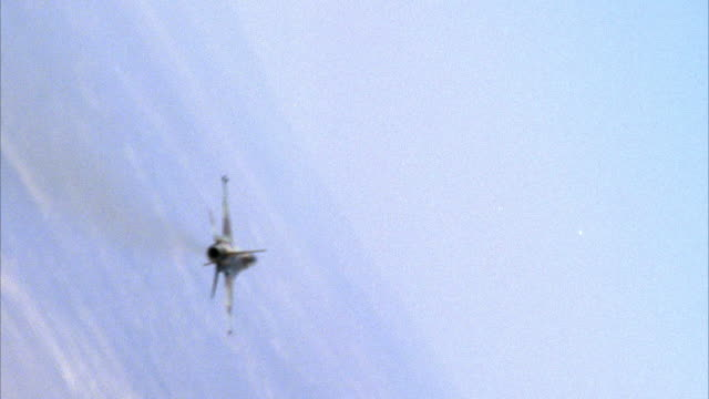 TRACKING SHOT OF A CAMOUFLAGE F-16 FIGHTER JET FLYING. THEN SEE TWO OTHER F-16 FIGHTER JETS ENGAGING IN A DOGFIGHT. SEE LAND BELOW. NEG CUT. ACTION.