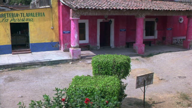 MEDIUM ANGLE OF PINK AND YELLOW BUILDING WITH SPANISH TILE ROOF. BUSHES. COULD BE MEDICAL CLINIC. SIGN IN SPANISH ABOVE YELLOW DOORWAY TRANSLATES TO 'HARDWARE AND BUILDING MATERIALS. RV WITH MOTORCYCLE ON ROOF PARKS ON ROAD IN FRONT. VILLAGES.