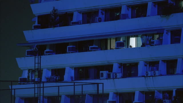 medium angle of side of white multi-story apartment building or hotel. see balconies in front of windows and air conditioners along side of building. - bangkok stock-videos und b-roll-filmmaterial