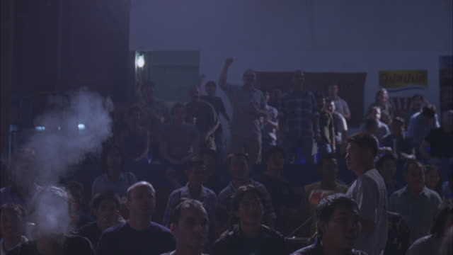 medium angle of audience in bleachers facing camera and cheering. could be small sports arena. man selling concessions to spectators. smoke. crowds. - stabilimento sportivo video stock e b–roll