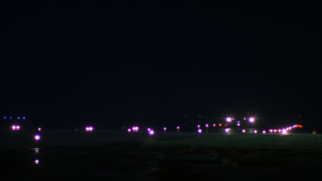 MEDIUM ANGLE OF AIR FORCE ONE JET AND SEVERAL MILITARY JEEPS DRIVING DOWN RUNWAY TOWARD AND PAST CAMERA.