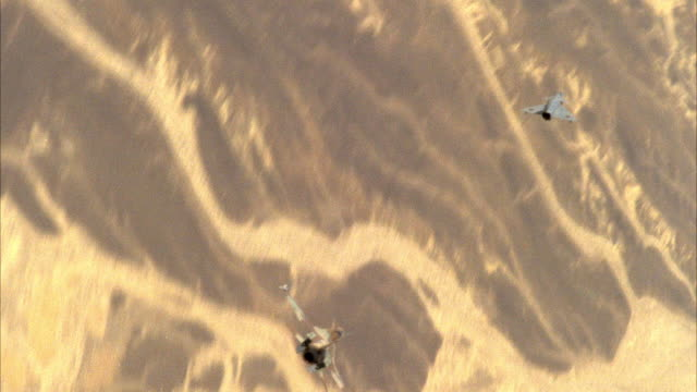 TRACKING SHOT OF TWO CAMOUFLAGE F-16 FIGHTER JETS FLYING. SEE JETS ENGAGING IN A DOGFIGHT. SEE LAND BELOW. NEG CUT. ACTION.