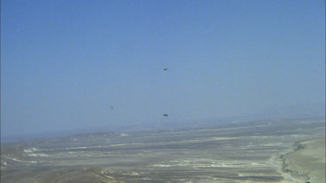 TRACKING SHOT OF TWO CAMOUFLAGE F-16 FIGHTER JETS FLYING IN DISTANCE. SEE THIRD JET FURTHER AWAY AND FLYING IN OPPOSITE DIRECTION. SEE DESERT AREA BELOW. MIDDLE EAST.