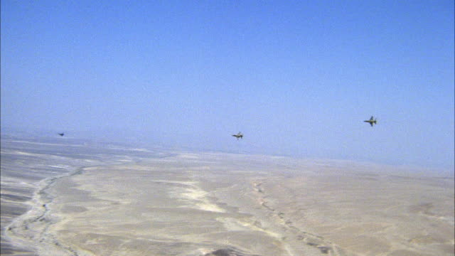 tracking shot of three jets flying farther away into distance. see mountainous desert plains below. middle east. - fighter stock videos & royalty-free footage