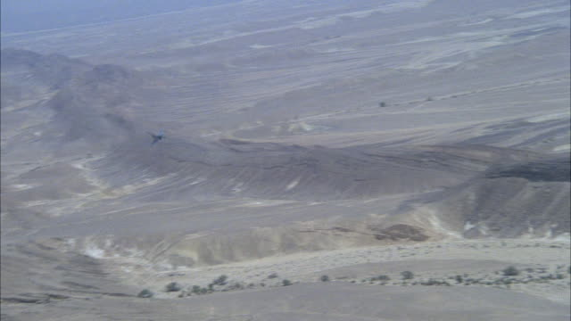 TRACKING SHOT OF A CAMOUFLAGE F-16 FIGHTER JET APPROACHING FROM DISTANCE. THEN SEE TOP AND REAR VIEW OF JET. SEE DESERT AREA BELOW. MIDDLE EAST.