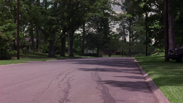 medium angle of two lane street in upper class residential neighborhood. see lush green trees flanking road. see speeding black 1993 cadillac fleetwood swerve as it drives towards camera. - cadillac stock videos & royalty-free footage