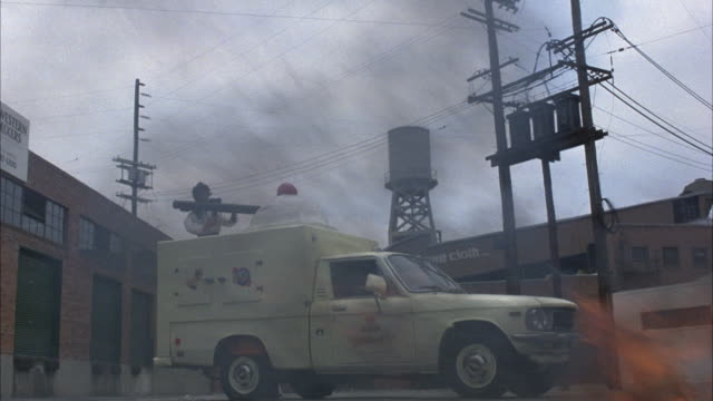 medium angle of ice cream truck or pickup truck with fire in the foreground. see plastic ice cream scoop and mannequin with bazooka. see warehouse in background. - アイスクリームスクープ点の映像素材/bロール