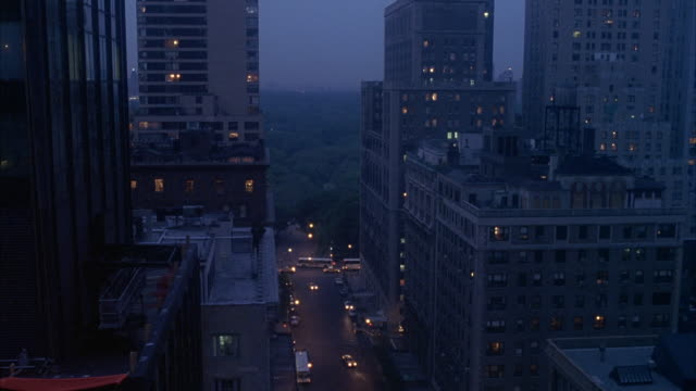 vidéos et rushes de wide angle of high rise buildings, in midtown manhattan. apartment buildings, condominiums or office building. could be upper east side. central park in background. cars, traffic visible in street below. - central park manhattan
