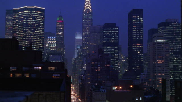 wide angle of new york city skyline. see lights from office building windows and headlights from cars below. - 1995年点の映像素材/bロール