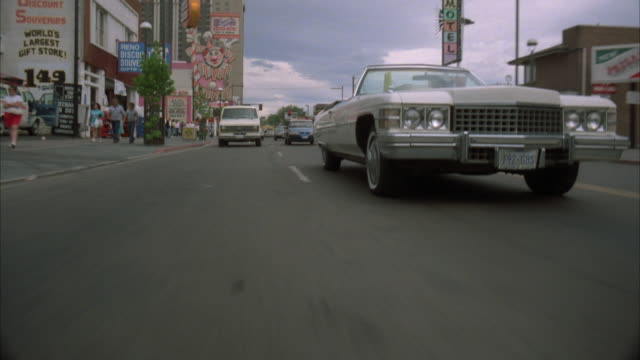 stockvideo's en b-roll-footage met process plate of a white ford e-150 van chasing a white cadillac convertible. see van bump side of cadillac. see parking lots and buildings in background of one way street. - 1980 1989