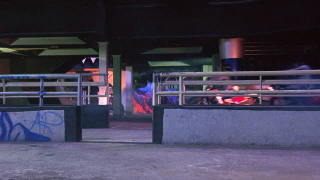 medium angle of motorcycle gang driving through warehouse. several men on motorcycles maneuver through pillars, railings, and walls. could be parking garage. walls have graffiti. could be chase. - biker gang stock videos & royalty-free footage