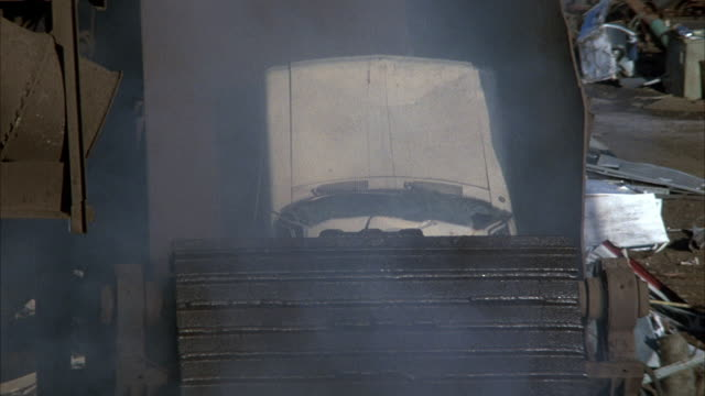vidéos et rushes de medium angle of white junk car falling off ramp to rotating grinder. other small pieces of metal fall into grinder. there is smoke or steam from the grinder. machine has dust and is rusty. - turning on or off