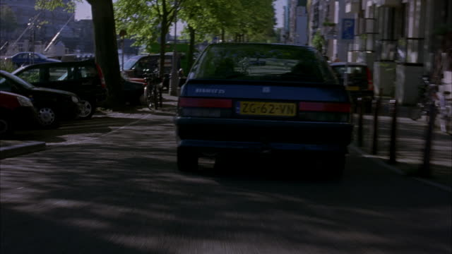 MEDIUM ANGLE OF BLUE RENAULT WITH DRIVER AND PASSENGER. POV FOLLOWS CAR DRIVING DOWN AMSTERDAM STREET. SEE CANAL, TREES, PARKED CARS, PEDESTRIANS, HOUSES ON SIDES OF STREET.