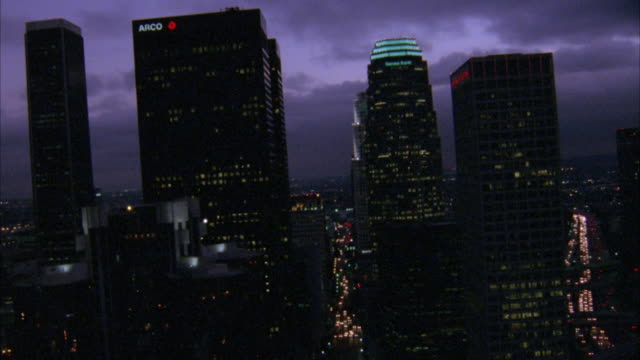 aerial of los angeles city skyline. flying pov as small airplane or helicopter flies through cluster of skyscrapers. see street and city lights below. - 1986 stock-videos und b-roll-filmmaterial