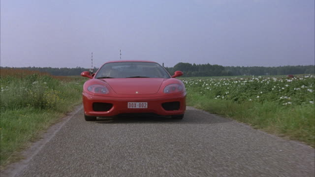 PROCESS PLATE OF FRONT OF RED FERRARI DRIVING DOWN COUNTRY ROAD. SEE TALL GREEN CORN PLANTS ON LEFT AND WIRE FENCE LINING FIELD ON RIGHT. SEE EUROPEAN LICENSE PLATE ON FERRARI READING DOX-002. MATCHING PLATES 2360-005 TO 2360-009.