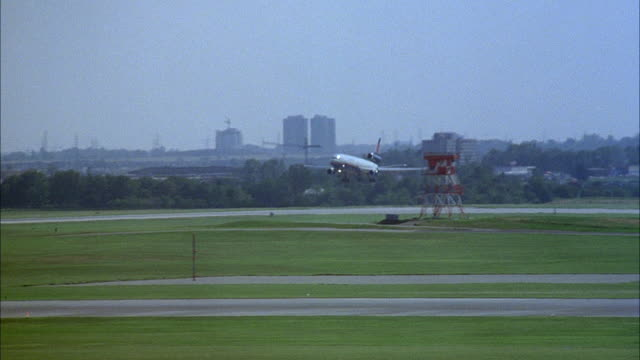 tracking shot of commercial airliner landing on runway at airport, skyline in background. pov from inside terminal - luftfahrzeug stock-videos und b-roll-filmmaterial