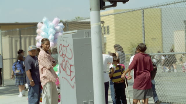 medium angle moving pov of street corner in front of school with children and parents. see men selling cotton candy and balloons. see playground with children in background behind chain link fence. - selling stock videos and b-roll footage