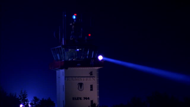 PAN LEFT TO RIGHT OF AIR TRAFFIC CONTROL TOWER WITH SPOTLIGHT SHINING DOWN. CAMERA PANS TO RIGHT TO REVEAL AIR FORCE ONE JET DRIVING TOWARD AND STOPPING IN FRONT OF CAMERA.