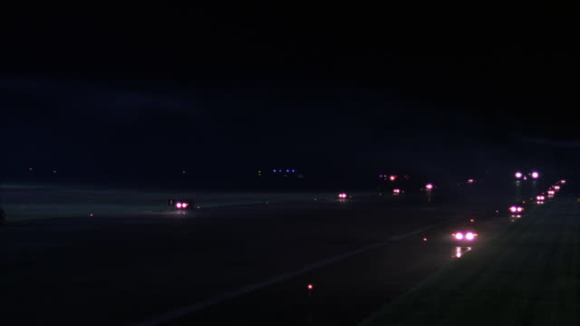 MEDIUM ANGLE OF AIR FORCE ONE JET DRIVING DOWN RUNWAY IMMEDIATELY FOLLOWED BY SEVERAL EMERGENCY VEHICLES WITH LIGHTS AND SIRENS ON.