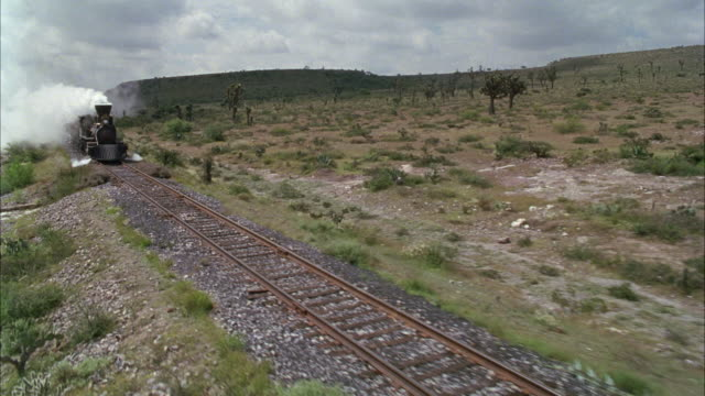 stockvideo's en b-roll-footage met medium angle of train moving down railroad tracks in desert or arid region. see white steam rise from engine of train. see green trees, brush, and cacti in surrounding area. see small hills or mountains in background. - locomotief