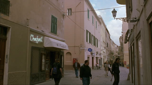 WIDE ANGLE OF NARROW STREET IN ITALIAN CITY OR TOWN. MEN WITH BACKPACKS AND WOMEN WITH PURSES WALK PAST CAMERA. SEE MAN ON  BICYCLE. SEE STOREFRONTS. STREET IS PAVED STONE OR BRICK. SEE NEON SIGN AND AWNING OVER ONE STORE OR RESTAURANT.